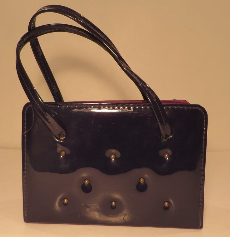 Vintage chic black studded handbag, '60s.   Chic black studded faux patent leather 1960s handbag featuring brass coloured studs. Lined in dark purple and black fabric with a gold clasp. One additional inner 'card' pocket. Fantastic condition.    Measurements: H:5.5, L: 8, W: 3.5 Label: None Decade: 1960s Material: Faux patent leather outer, fabric inner