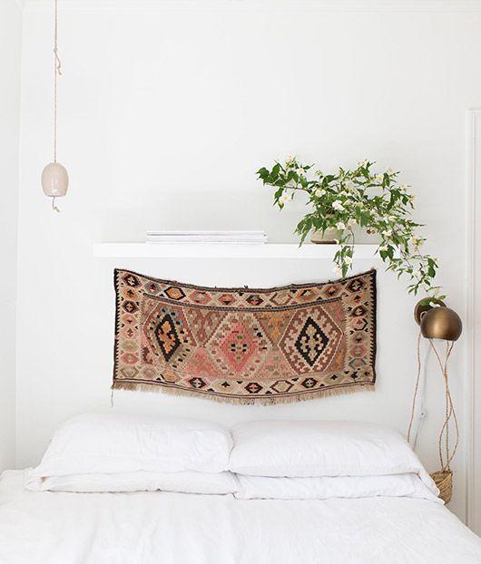 Wandteppich als Kopfteil hinter dem Bett