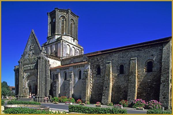 Façade Nord de l'église Notre-Dame de Vouvant des XIe et XIIe siècles, avec ses puissant contrefort et son double portail roman surmonté d'un vaste fronton gothique;