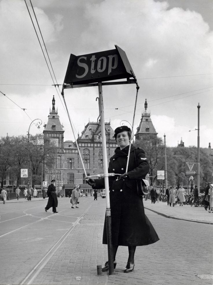 1955 Vrouwelijke politie of verkeers-agente regelt met een stopbord het verkeer voor het centraal station te Amsterdam, Nederland 1955.