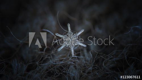 Snowflake on dark textured background: macro photo of real snow crystal on black woolen fabric in natural light. This is panoramic version (widescreen) of unusual snow crystal, resembles ship's wheel.