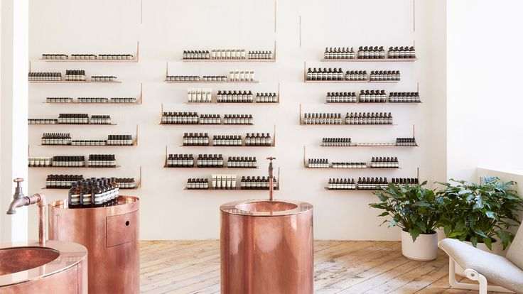 Thin copper shelves match cylindrical sinks at this Aesop store close to San Francisco's waterfront by New York studio Tacklebox.