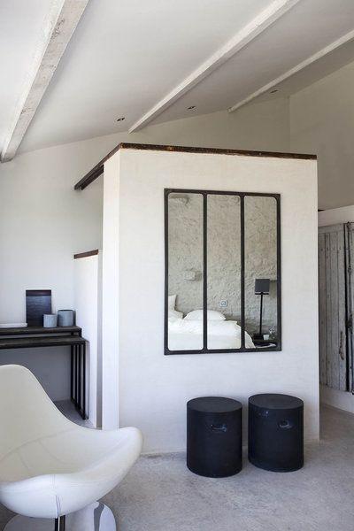 Murs recouverts de plâtre pour cet espace où la salle de bains se cache derrière un volume intérieur maçonné.