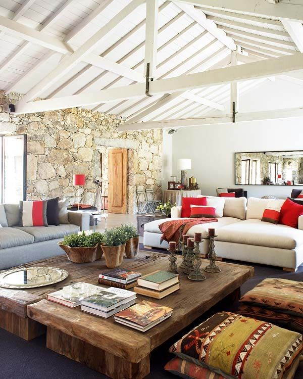 <3 the table, stone wall, beamed ceiling, and comfy shape of the white sofa