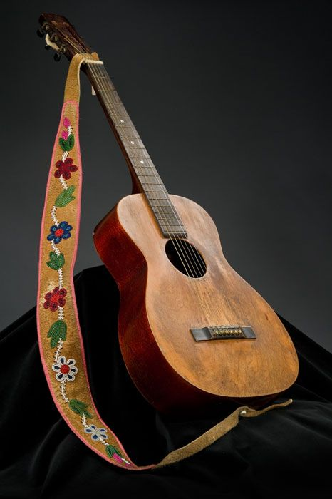 Guitar and Strap Métis. c Mid 1900's.  Archie Calliou: a champion old-time fiddler, he formed a country and western band in which he played fiddle and guitar. The Northern Echoes performed at the Grand Ole Opry and cut a single in Nashville. Mr. Calliou's guitar was a treasured gift from Canadian country star Wilf Carter. Mr. Calliou added the beaded hide strap.