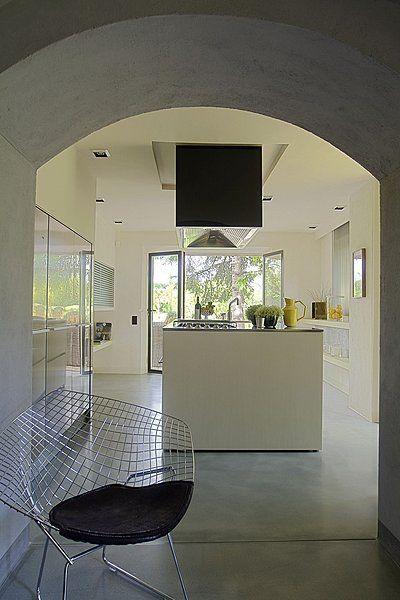 Derrière la chaise « Diamond » de Harry Bertoïa, la cuisine en inox et bois blanchi, équipée par Boffi est largement ouverte sur la terrasse avec accès privatif sur le parc, table et sièges de salle à manger Sempré
