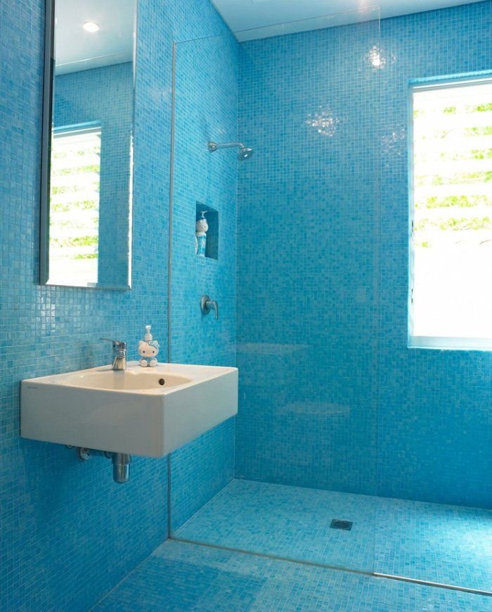 Stanza da bagno per bambini minimal rivestito con piastrelle a mosaico blu, con lavabo a parete e doccia a filo pavimento