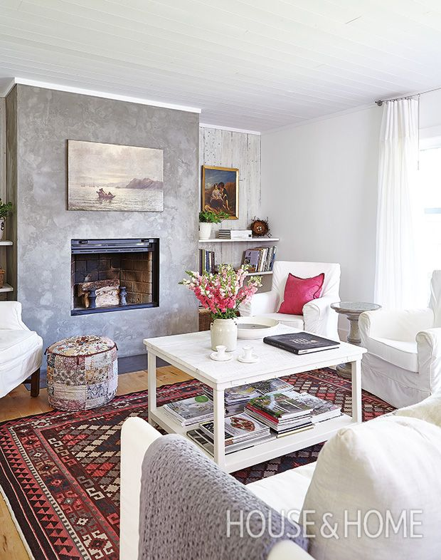 In this Paris-meets-Provence living room, a modern concrete fireplace is softened with pops of pink, white linen chairs and white-washed barn wood. | Photographer: Valerie Wilcox | Designer: Vi Jull