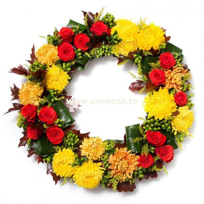 Coroana funerara flori de toamna, transmite liniste, pace si ganduri calme celor dragi in aceasta perioada grea. Coroana este creata din: crizanteme dahlii, trandafiri rosii, hypericum si frunze de toamna.