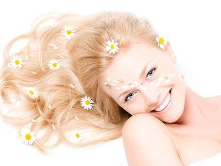 Красивая блондинка с голубыми глазами и ромашками на волосах