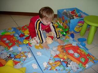 Tappeto gioco in spugna        Cosa serve:      spugna alta cm 4    stoffa di cotone colorata    laccetti    velcro    Per fare questo tappeto gioco ho tagliato una spugna in 4 quadrati uguali 56×56 cm.    Ho rivestito la spugna con della stoffa per bambini colorata (io ho scelto come fantasia l'arca con gli animali) , applicando lungo un bordo del velcro in modo da poter sfoderare e lavare il tappetino ogni qual v