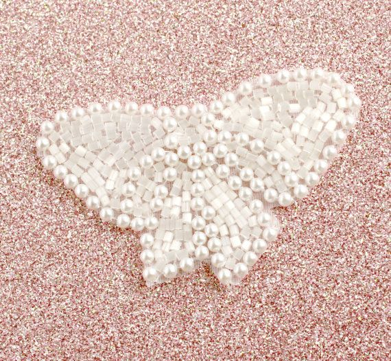 Lovely bow-shaped beaded applique of white satin finish beading and faux pearls.  Perfect for garters, shoe clips, head pieces, etc.!