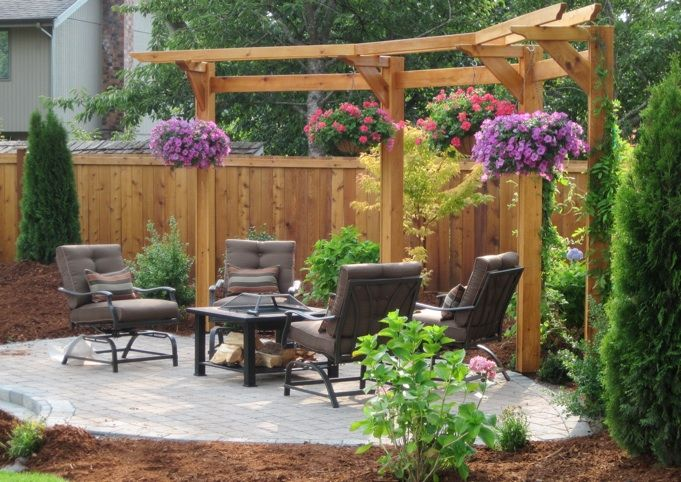 This 4 Post arbor & trellis system around a paver patio provides a picturesque backdrop for an intimate get together.  The hanging planters provide above the fence screening.