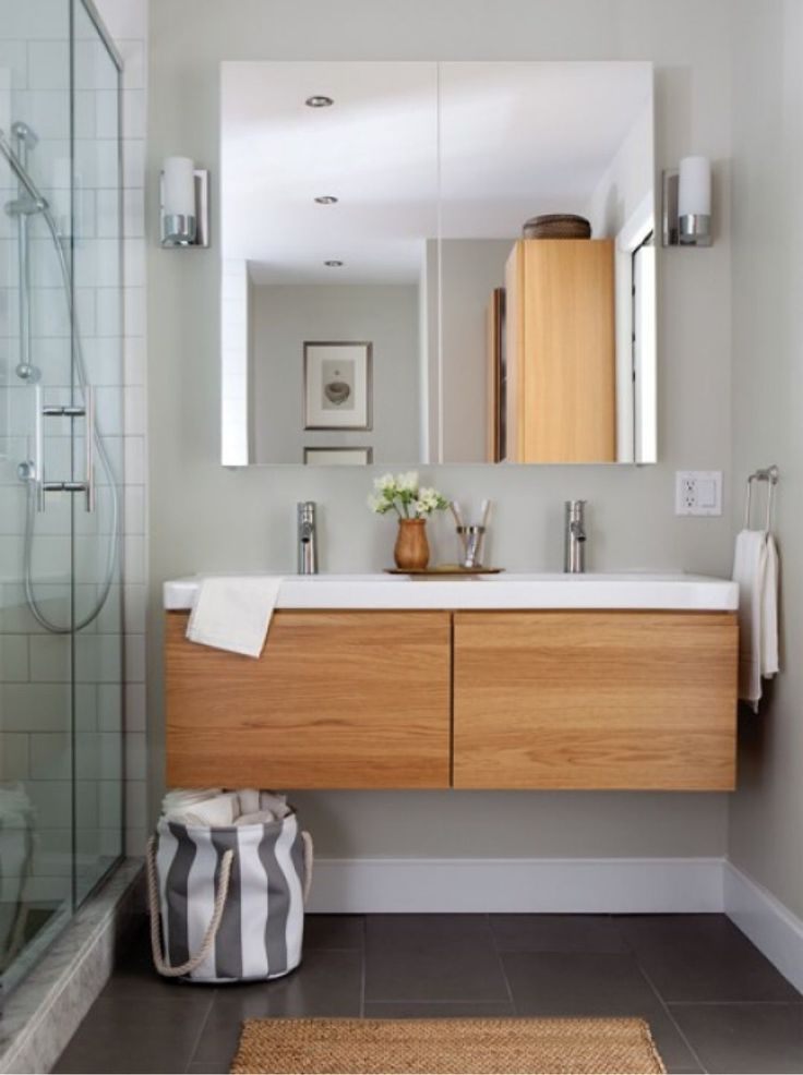 We like this colour combination of the walnut wood, charcoal floor and white sink. However, we would want white walls.
