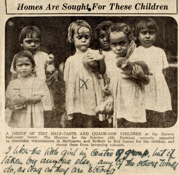 A group of six small children wearing plain white frocks and holding soft toys, the child in the centre has been marked with a havdwritten cross