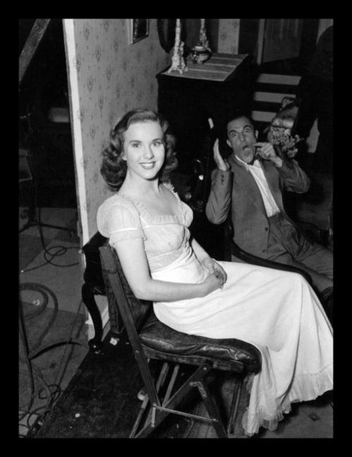 Gene Kelly messing around in the background of this photo taken backstage on the set of 'Christmas Holiday.' Deanna Durbin doesn't seem to notice.