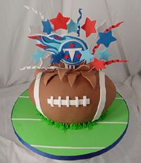 tennessee titans logo popping out of exploding football cake set on a green football field