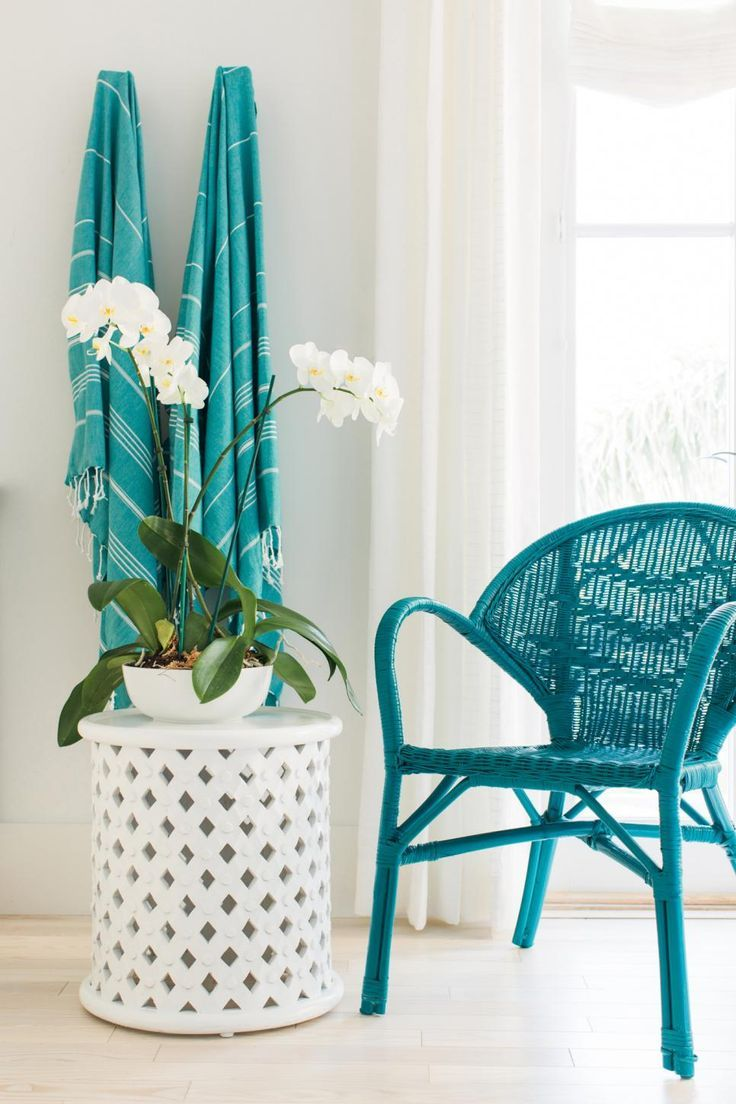 Wicker, striped towels and a blooming orchid on a white ceramic stool accent the room beautifully.