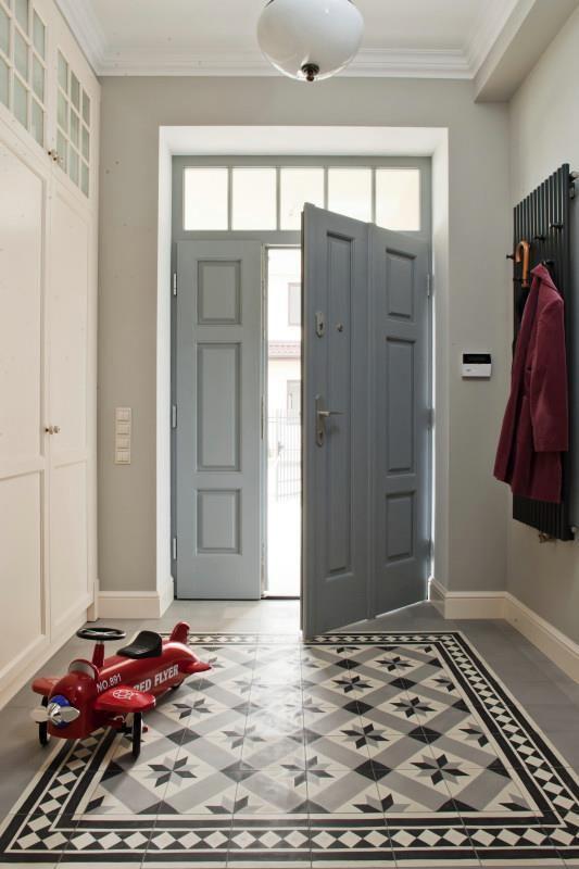 Przedpokój ze stylową białą szafą i nowoczesnym wieszakiem na okrycia wierzchnie zdobi wzorzysta podłoga / Simple and warm hallway.