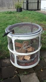 This is a picture of a cylindrical firepit. It is formed from a repurposed 55 gallon steel drum, metal plate and tubing, and expanded metal mesh.