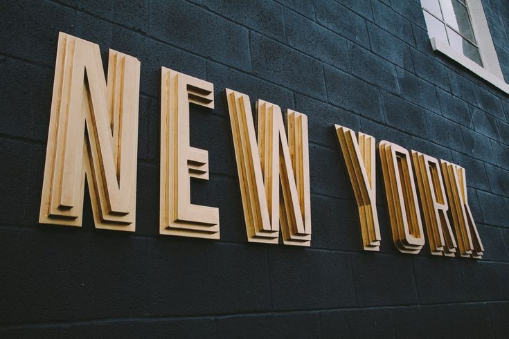 """SIDESHOW SIGN CO """"New York"""" gold layered sign on black wall."""