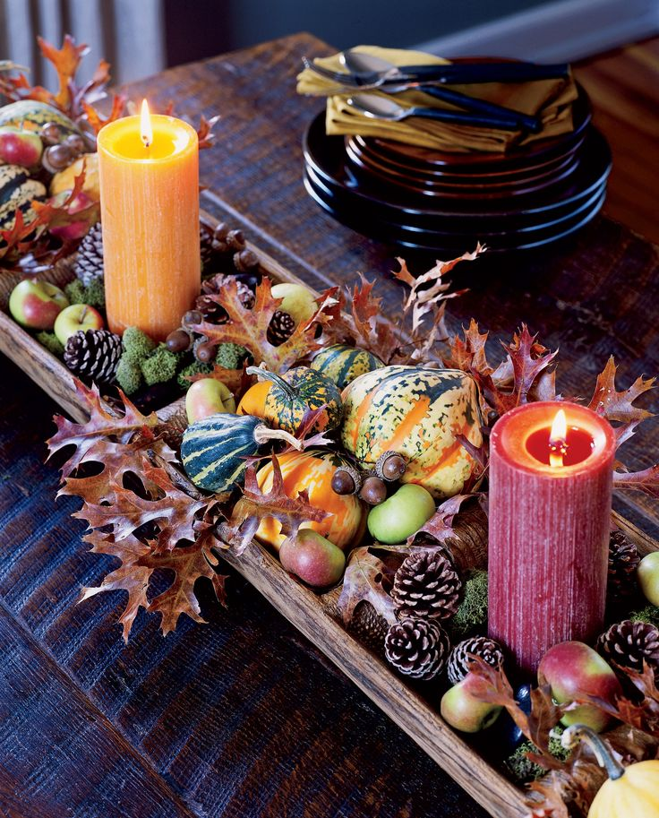 An Antique Dough Riser is the foundation for this lush centerpiece of autumn-hued pillar candles and a variety of tiny gourds, squash, cones, and pods. Adapt this idea to any shallow box or tray you may currently have. Oak leaves, acorns, and moss can be collected during an afternoon forest walk or from a trip to the local craft store.  A long, low centerpiece such as this looks as pleasing on an entry table or sideboard as it does on the dining table. It's also great for parties since it…