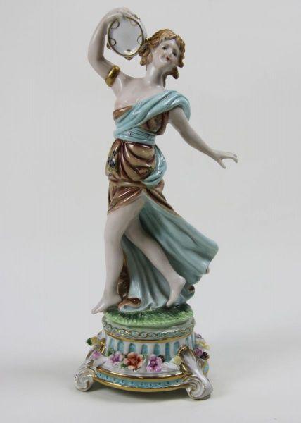 Royal Crown Derby Magnífica escultura em porcelana representando dançarina tocando címbalo. Base extraordinária com flores em relevo. Arremates em ouro. Peça de coleção! Pertencente ao período de Crown Derby de 1877-1890. Inglaterra, sec. XIX. 36 cm de altura