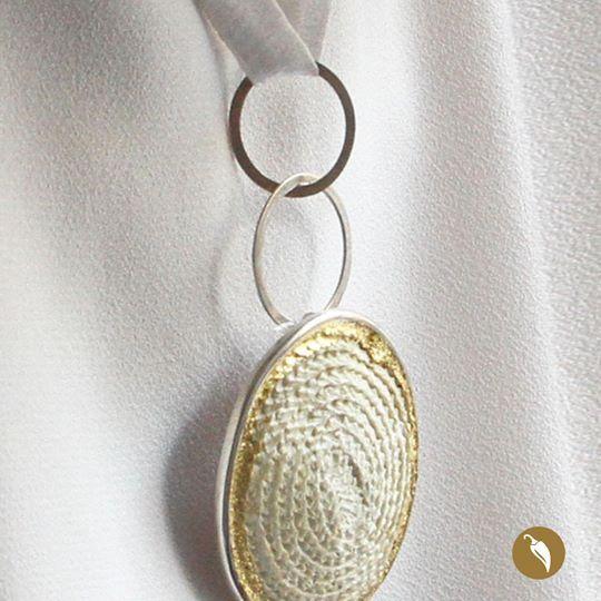 Monoco en su constante experimentación también ha incursionado en la porcelana. Este espectacular colgante ajustable mediante una cinta de seda natural, es uno de los resultados de este proceso. La pieza de porcelana esta realizada a partir de una pieza de teatina tejida y engastada en plata. Se pueden apreciar las huellas de las fibras vegetales. La orilla ha sido iluminada con pan de oro de 22 kilates, es reversible, su segunda cara es una pieza de plata con un diseño perforado. Pieza…