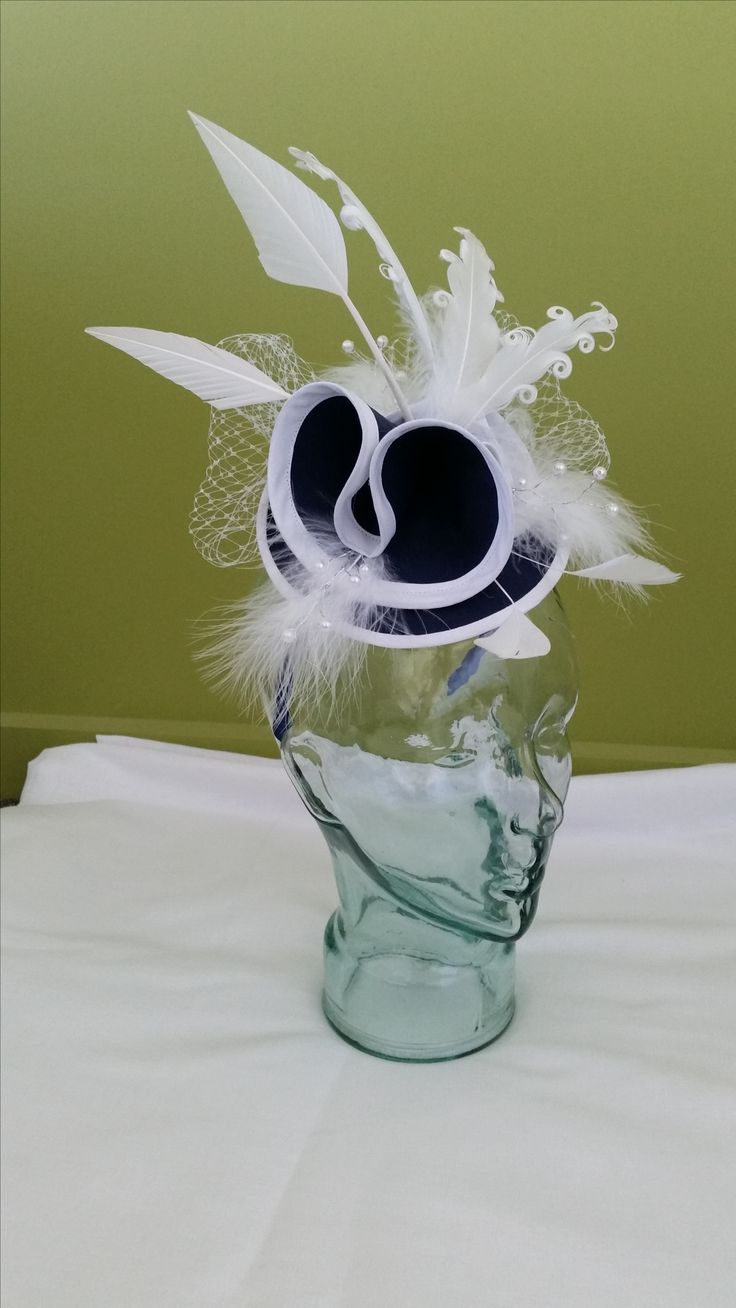 An elegant structural navy and white fascinator.  The feather are giving in balance and style