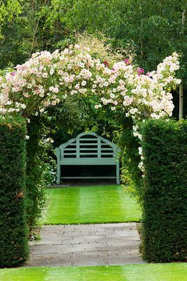 Rose arch in an English country garden by photographer Clive Nichols