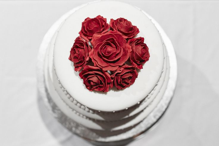 Colour pop of gorgeous red roses on a classic wedding cake. Captured by Adam Popovic Photography. Auckland wedding photographer.