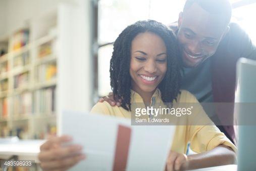 Stock Photo : Happy couple reading paperwork at laptop
