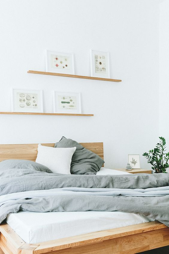 Nyde loves this white Scandi bedroom with natural wood accents - it creates a minimalist haven for relaxation. Read more at: https://nyde.co.uk/blog/scandi-rooms-natural-wood-trend/