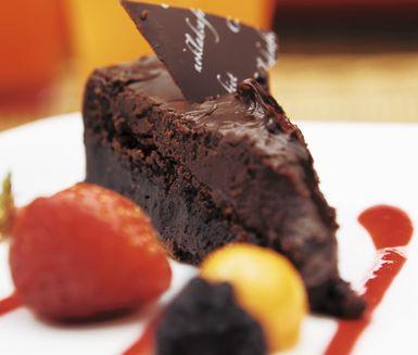 """Ett smaskigt recept på mustig kladdkaka att servera till kaffet. Chokladkaféets kladdkaka täcker du med en delikat glasyr av grädde, honung, socker, choklad och smör och serverar med en utsökt hallonsås. Perfekt att servera till efterrätt! <a href=""""http://www.ica.se/recept/kladdkaka/""""> Här hittar du fler härliga kladdkakerecept </a>."""