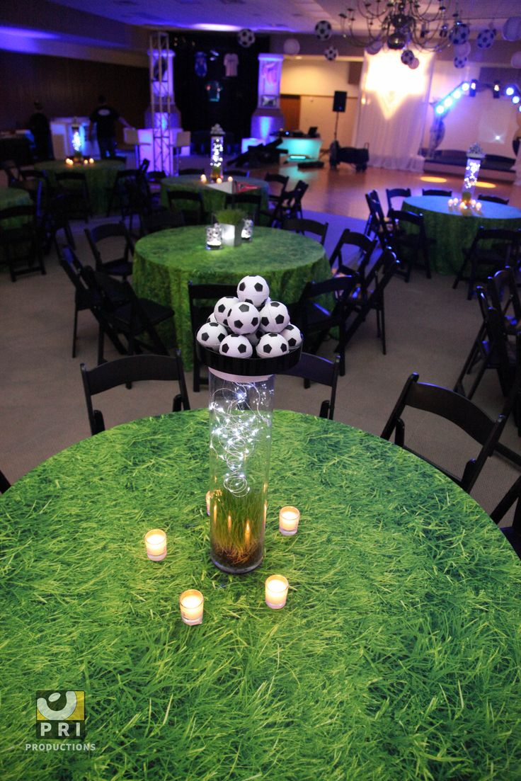 Soccer centerpieces for a sports themed event with grass patterned table linens.