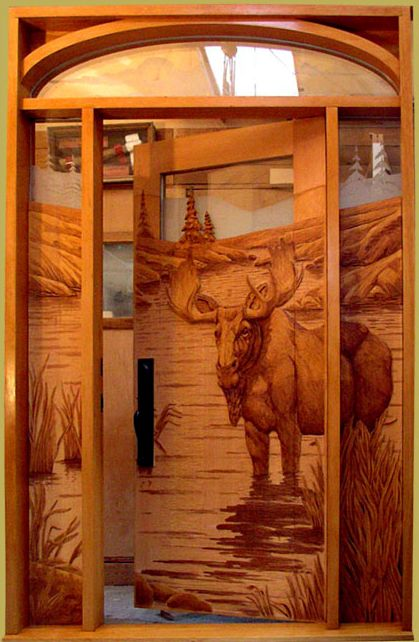Wood carved entry door with moose by summit log home
