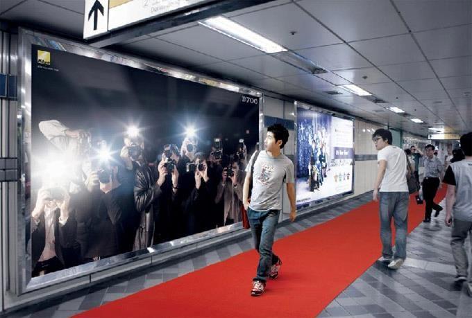 В оживена спирка на метрото в Сеул, Nikon монтират този огромен билборд, който кара всеки минувач да се почувства като знаменитост. Когато човек мине покрай него, автоматично се задействат мигащи светлини като светкавици от фотоапарат. Червеният килим, по който минават хората, продължава и извън пределите на метростанцията и изминава целия път до магазин на Nikon в близък мол.