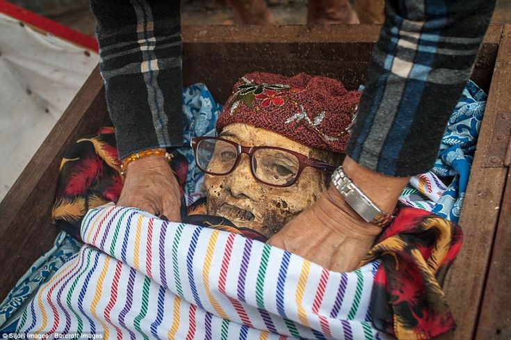 Relatives clean the body of Ne'Tampo, dead for 30 years, during the Ma'nene ritual at Panggala Village