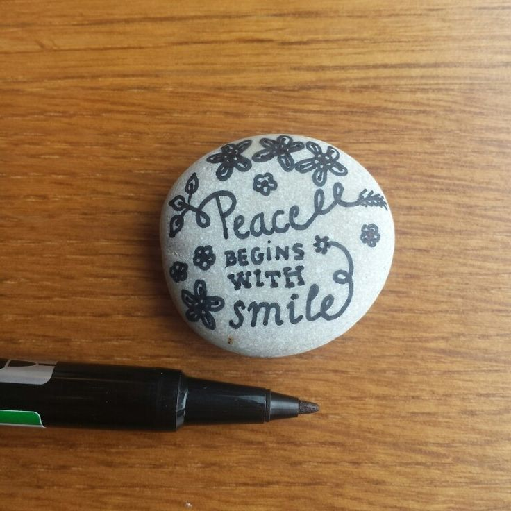 """"""" peace begins with smile """" drawing on the rock"""