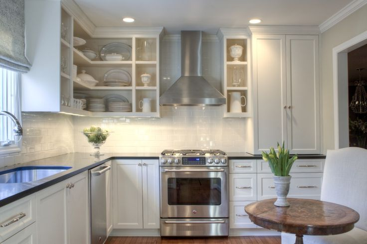 Allison Harper Interior Design - Interiors White kitchen; white subway backsplash; simple shaker cabinets to ceiling with crown moulding; dark grey counter tops; stainless appliances; small pops of color in the accessories (flowers) and warm wood accents