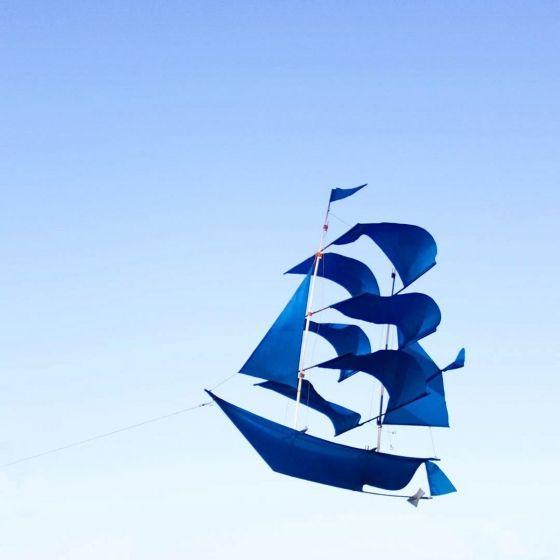 Cerf-volant bleu roi en nylon et bambou fait à la main par des artisans balinais. Il se transforme en bateau volant lorsque le vent s'engouffre dans ses voiles et sert de mobile décoratif lorsqu'il est suspendu en intérieur.