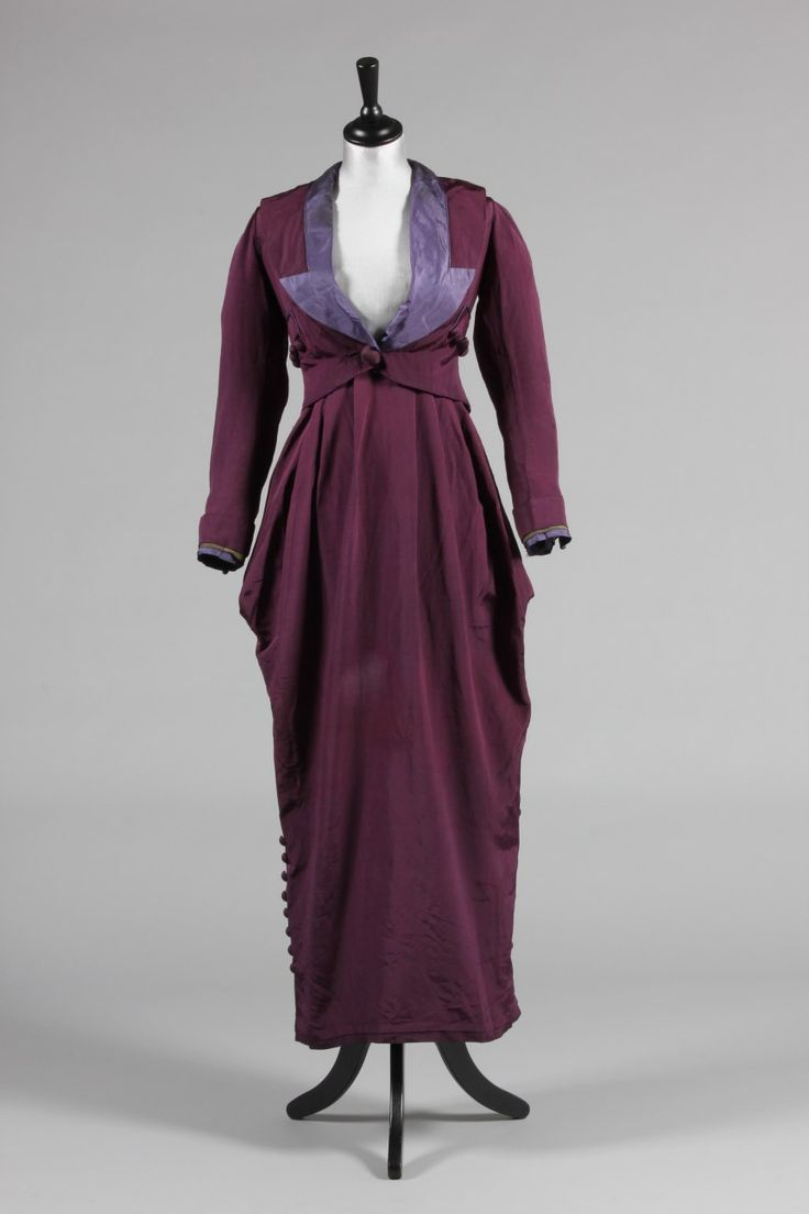 A rare Charles Drecoll purple faille walking suit, circa 1911-14, labelled 'Ch Drecoll, Vienna & Paris', the jacket faced in lilac silk, also with silver braid to the cuffs, weighted rectangular tail to the back with button detailing, buttoned faux pockets to the sides, barrel-shaped ankle-length hobble skirt with broad petersham inner waistband, - 1600 £