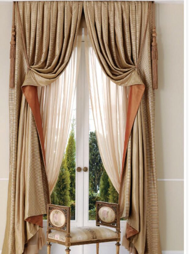 Layered Curtains Over A Pair Of Sheer Panels Are Pulled Up At High Sharp Angle To Reveal Contrasting Fabric On The Exterior Side