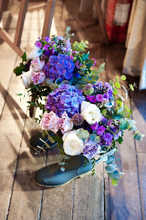 Purple wedding flowers in wellington boots created by Senses Floral Design and photographed by Juliet McKee