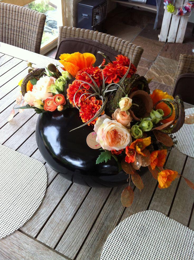 Oranje met zwart bloemstuk met dalia's, ranonkels en tillandsia.