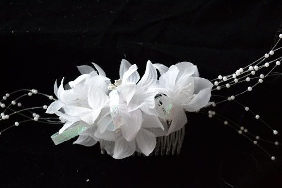 White sheer flowers with pearl like centres. Accented with pearl like sprays and white sparkly ribbon.