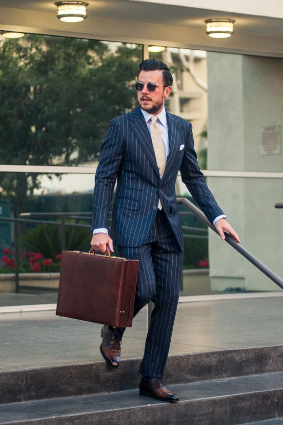 Maxwell Scott Strada attche case styled with a navy bespoke suit.