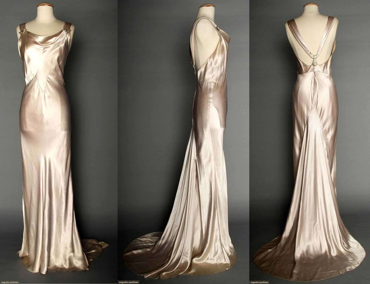 "SILVER SATIN EVENING GOWN, 1930s  Silver-pale lavender silk charmeuse bias-cut sleeveless gown, cowl neckline, open back, jeweled Deco elements on shoulder straps & at CB, floating trained back panel, labeled ""NRA Code, Made Under Dress Code Authority PHB038577"", B 34""-36"", H 35""-38"", L62""-72"", (belt missing, 3 tiny tears on front, stains & grime at hem) fair. Augusta Auctions. April 9, 2014 - NYC New York City"