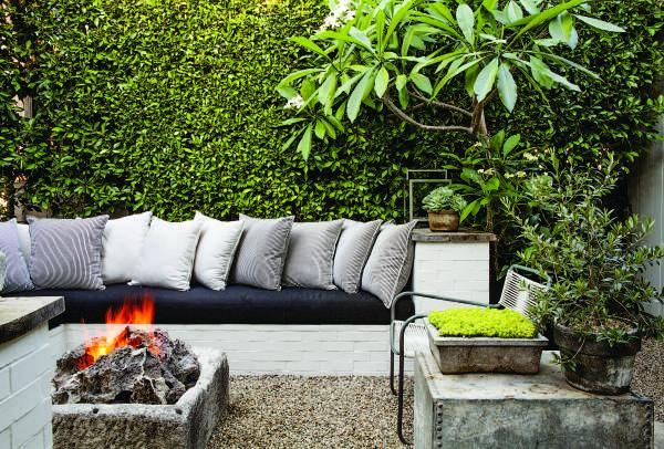 A seating area of the garden is built from brick to match the house, with the fire pit made from stone taken from an abandoned well in France. The side table, an upside-down metal planter, was salvaged — on top of it is an olive bonsai tree. In the upper right corner is plumeria, and the hedging is Ficus nitida.