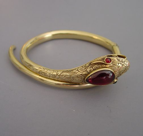 VICTORIAN karat yellow gold snake bracelet with garnet cabochons and faceted garnet eyes, etched design on snake's head.